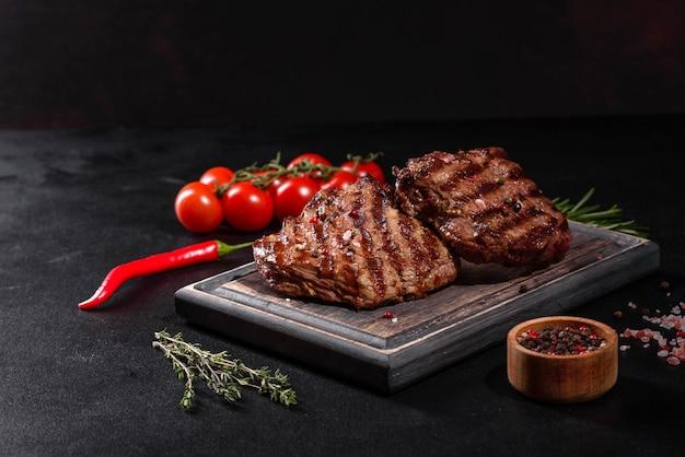 Свежий сочный вкусный стейк из говядины на темной поверхности. мясное блюдо со специями и зеленью