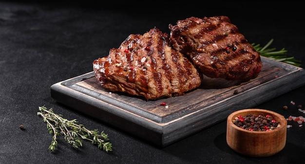 Свежий сочный вкусный стейк из говядины на деревянном столе. мясное блюдо со специями и зеленью