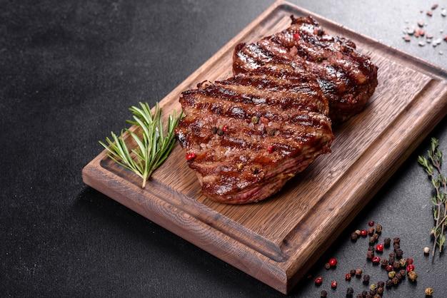 나무 테이블에 신선한 육즙 맛있는 쇠고기 스테이크. 향신료와 허브와 고기 요리