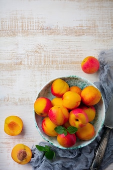 Fresh juicy fruit nectarines in ceramic bowl on white wooden.