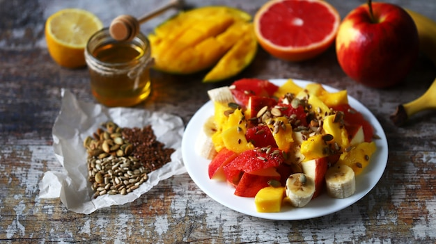 Свежий сочный фруктовый салат на тарелке с манго, грейпфрутом и семечками