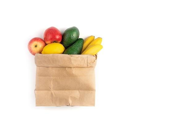 Свежие сочные плоды помещаются в бумажный пакет на белом фоне.