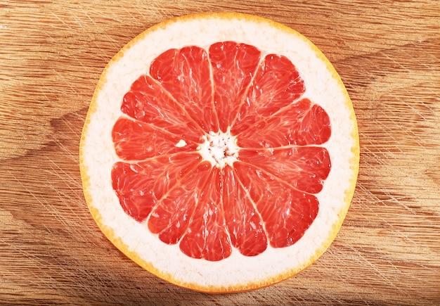 Fresh juicy grapefruit slices on wooden