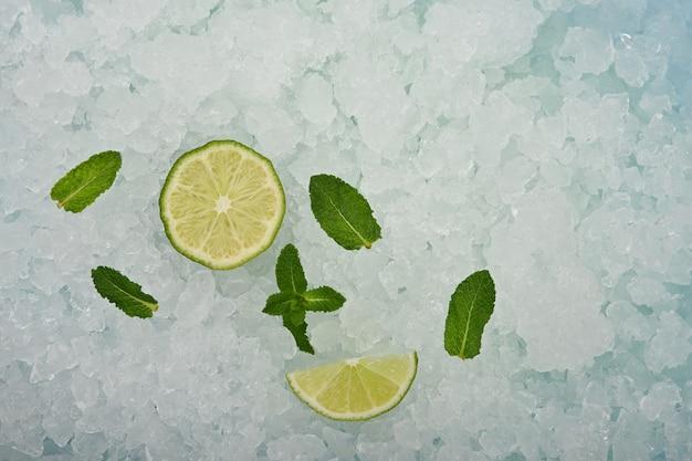 신선한 육즙이 많은 녹색 라임은 으깬 얼음 배경 위에 반으로 자르고 쐐기 조각과 민트 잎