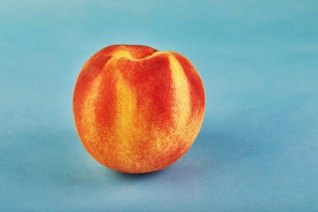 Свежий сочный персик на синем фоне
