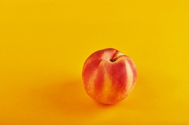 オレンジ色の背景に新鮮なジューシーなピーチ