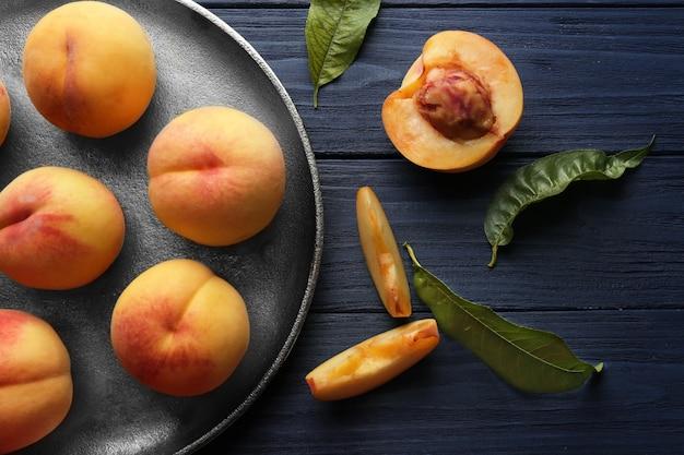 Свежие сочные персики в подносе на синем деревянном