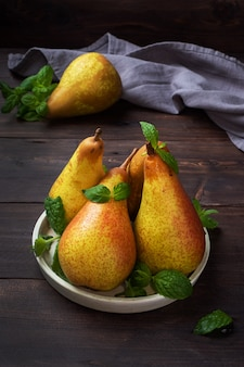 Fresh juicy pears in a bowl on dark wooden rustic background.
