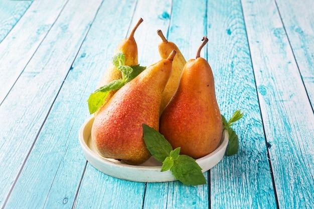 青い木製の明るい背景に新鮮なジューシーな梨会議。熟した果実の秋の収穫。コピースペース