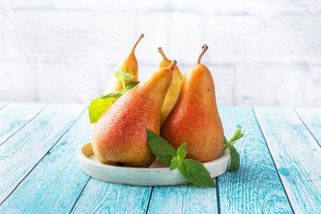 青い木の明るい表面に新鮮なジューシーな梨のカンファレンス。熟した果実の秋の収穫。コピースペース