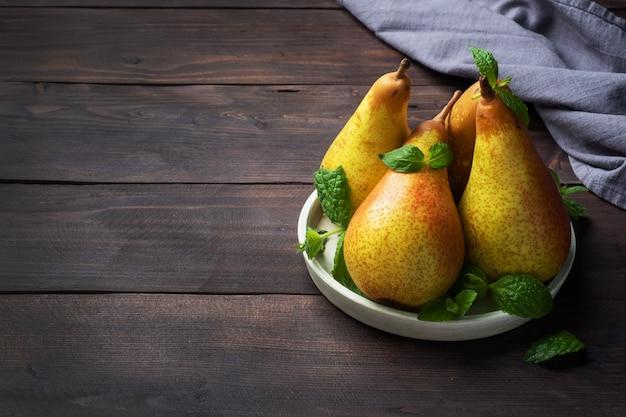 暗い木製の素朴な背景に新鮮なジューシーな梨のカンファレンス。熟した果実の秋の収穫。コピースペース