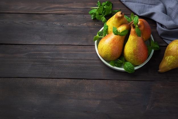ダークウッドの素朴な背景に新鮮なジューシーな梨会議。熟した果実の秋の収穫。コピースペース