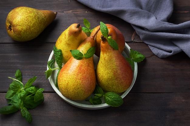 暗い木の素朴な表面に新鮮なジューシーな梨のコンファレンス。熟した果実の秋の収穫。コピースペース