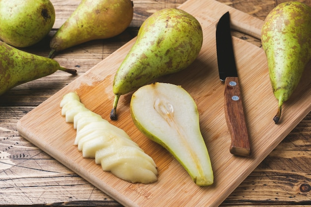 Fresh juicy pears conference whole and cut by slides on wooden rustic background.