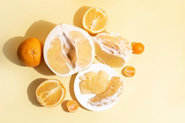 Свежие сочные половинки помело, дольки, мякоть, кожура, апельсины и мандарины в солнечном свете, крупным планом. цитрусовые.