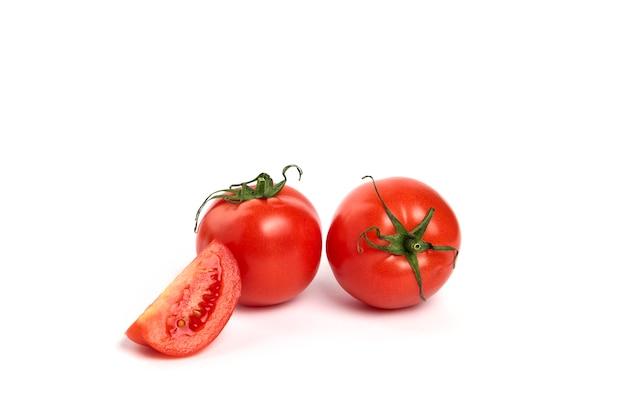 Pomodoro rosso succoso fresco con tagliato a metà isolato su priorità bassa bianca.