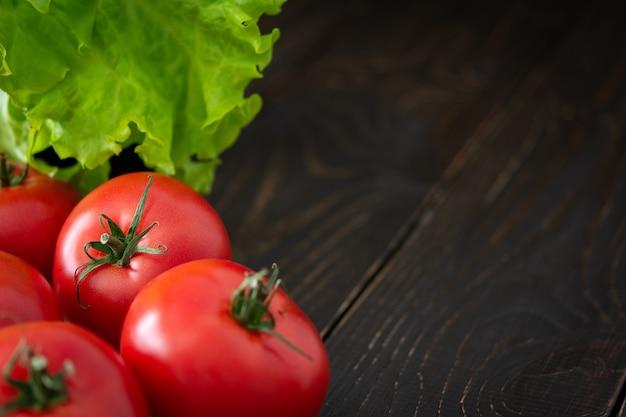 유기농 채소의 새로운 작물인 녹색 포니테일이 있는 신선하고 즙이 많은 익은 분홍색 토마토