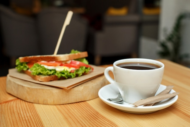 Fresh juicy sandwich with cup of hot coffee on wooden table with dark background