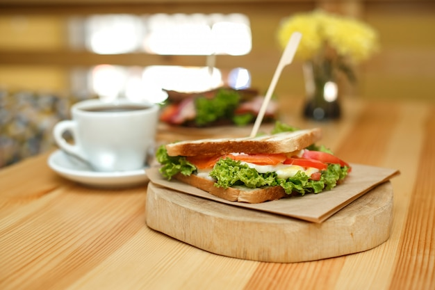 Fresh juicy sandwich with cup of hot coffee on wooden table with white blurred background