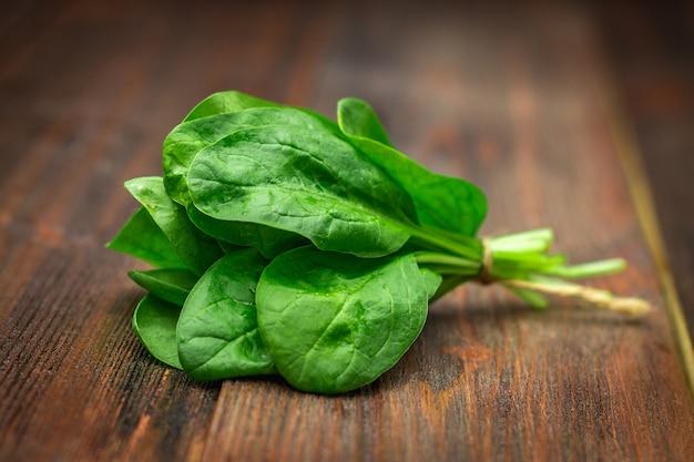 신선한 육즙 시금치 나무 갈색 테이블에 나뭇잎. 천연물, 채소, 건강 식품 프리미엄 사진