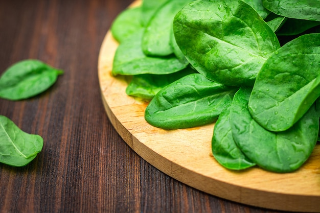 Fresh juicy spinach leaves on a wooden brown table. natural products, greens, healthy food
