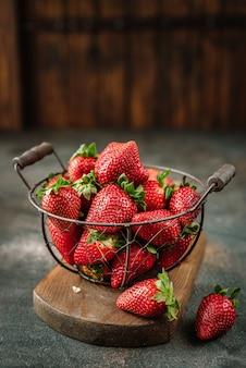Fresh juicy strawberries in basket with leaves on rustic background