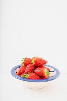 Свежие сочные клубники в керамической миске, изолированной над белым столом. вид сбоку. копировать пространство