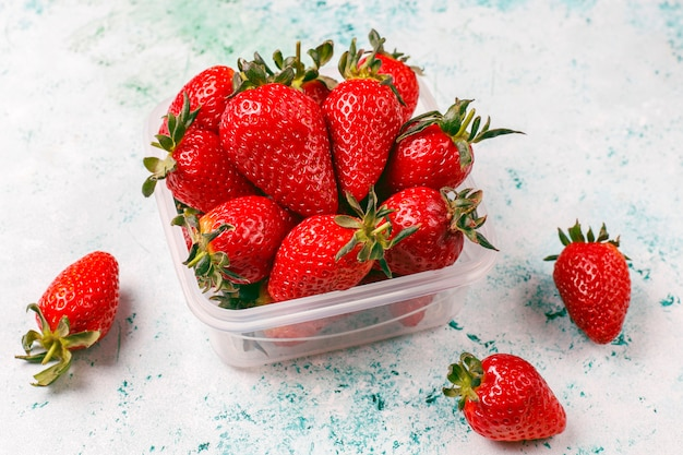 Fresh juicy strawberries in plastic lunch box on light