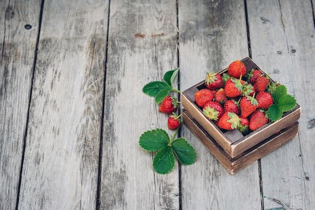 葉と新鮮なジューシーなイチゴ。素朴な木箱と手作りのレース。レトロな雑誌の写真。コピースペースのあるイチゴ。