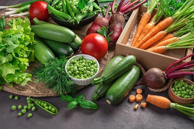 Свежие, сочные овощи и зелень на коричневом фоне. вид сбоку, горизонтальный. овощной фон.