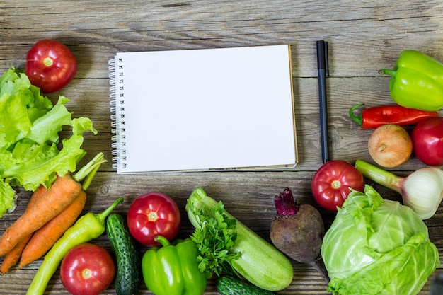 Fresh juicy vegetables border, blank white notepad, top view