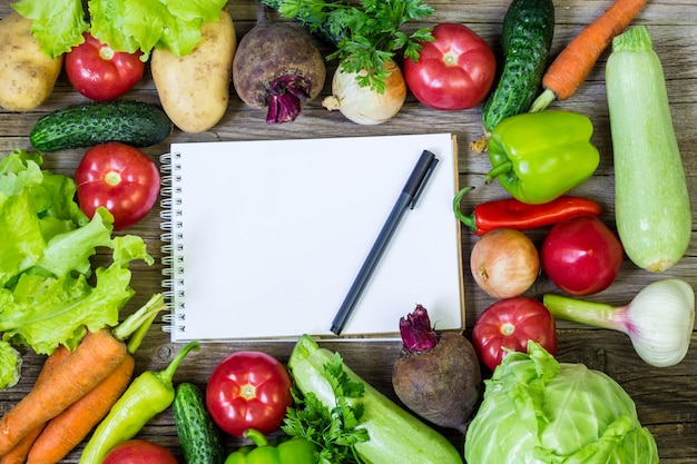 Fresh juicy vegetables border, blank white notepad with copy space and pen, top view.