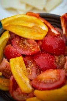 Свежие сочные овощи, перец, помидоры, нарезанные кусочками на тарелке. подготовка овощей к запеканию на гриле, вид сверху.