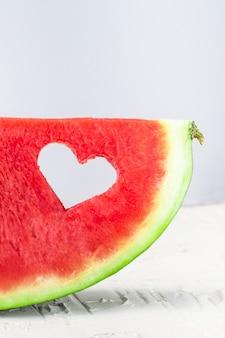 흰색 바탕에 하트 모양 구멍을 가진 신선한 육즙 수 박 조각. 발렌타인 데이, 사랑, 여름 개념 복사 공간