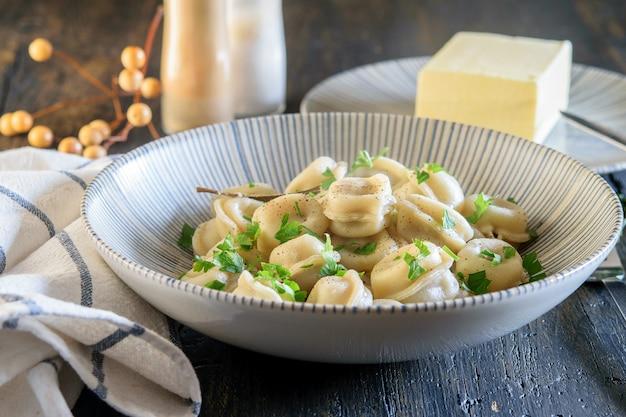 暗い木製のテーブルの上に青いボウルに緑とバターを入れた、焼きたての自家製餃子。