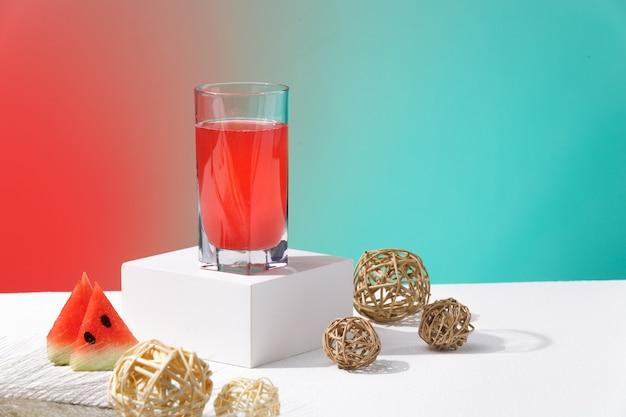 赤と青の背景に新鮮な絞りたてのスイカ飲料