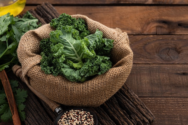 Fresh kale in sack on wood background
