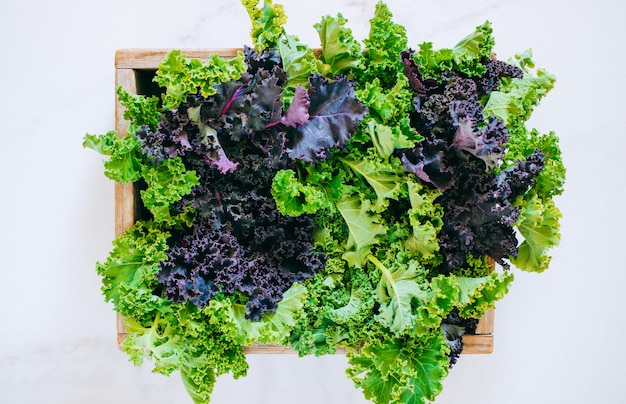 Fresh kale in a wooden box on a marble background