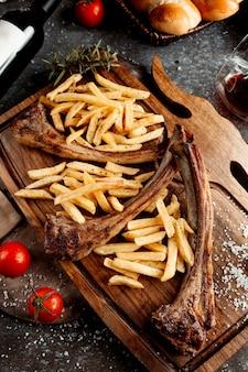 Свежий шашлык с картофелем фри на деревянной доске