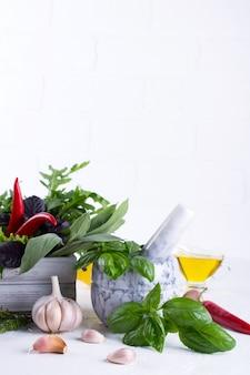 Свежие кухонные травы и специи, масло с белым керамическим раствором. салат из базилика с укропом и шалфеем с рукколой