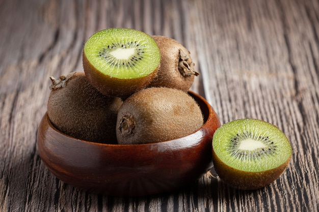 Fresh kiwi, cut into half, put on a wooden bowl