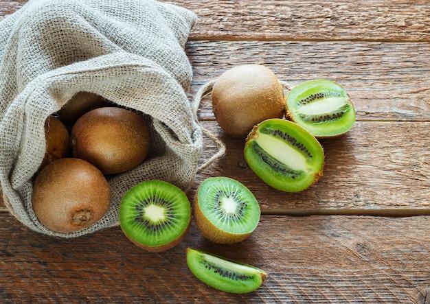 Fresh kiwi fruit in bag on brown wooden surface
