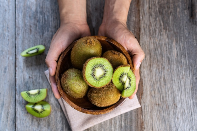 Fresh kiwi fruit in the bowl on wooden surface