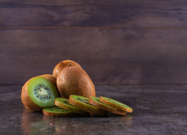 Fresh kiwi fruit on dark surface