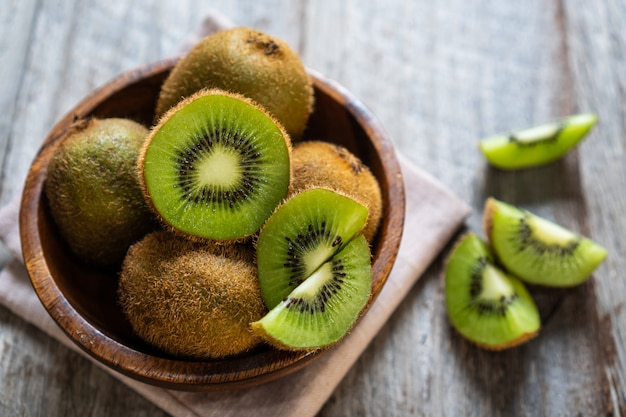 나무 배경에 그릇에 신선한 키 위 과일