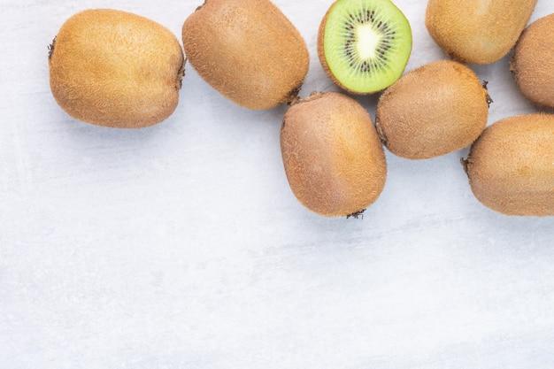 Fresh kiwi fruits, whole and sliced, on the marble.