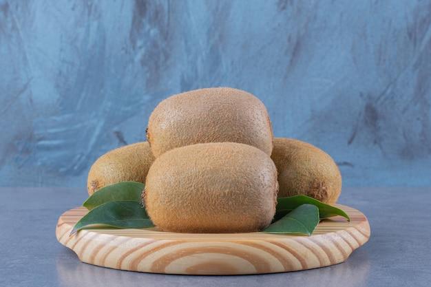 Kiwi freschi su un piatto di legno sulla tavola di marmo.