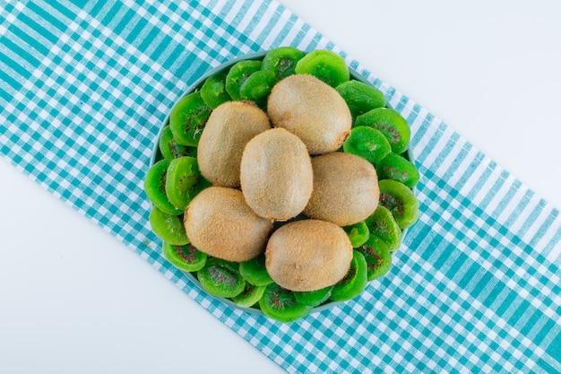 白とピクニック布の背景に平らな乾燥したキウイとプレートの新鮮なキウイを置く