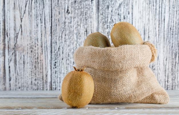 木製のテーブルの袋に新鮮なキウイ。側面図。