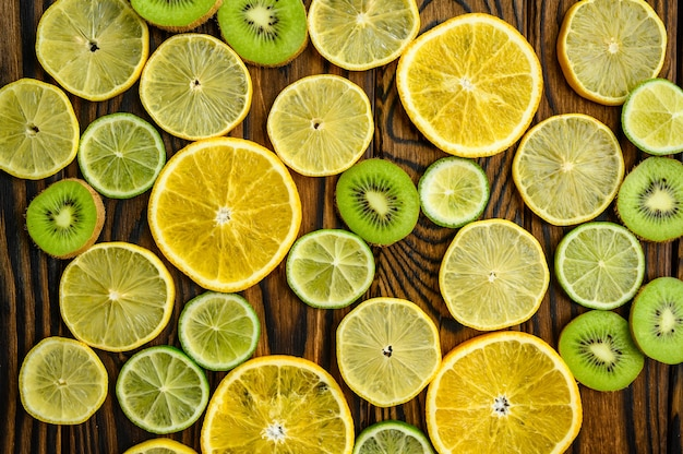 Fresh kiwi and lemon slices on wooden background, top view. organic vegetarian food, grocery assortment, natural eco products, healthy lifestyle concept